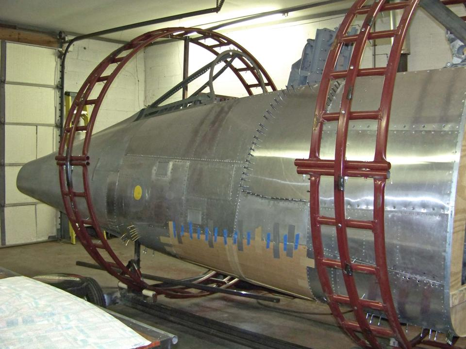 A picture of the cardboard gun bay door taped to the fuselage frame. 